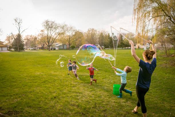 Enfants qui jouent à faire des bulles dans le jardin