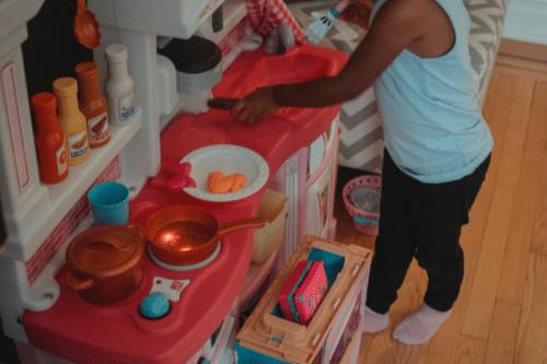 Petite fille qui joue avec une cuisine jouet