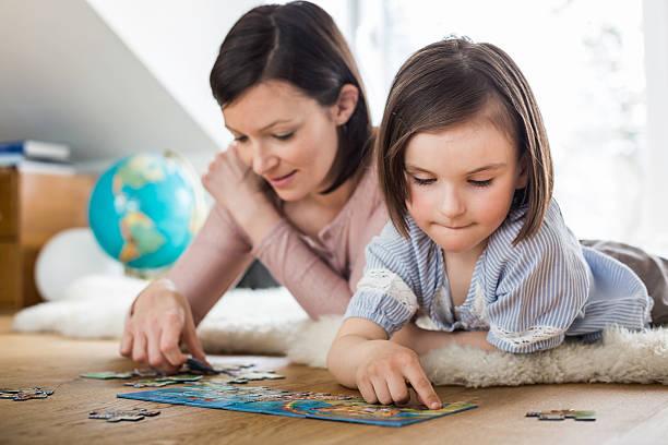 Petite fille qui fait un puzzle avec sa maman